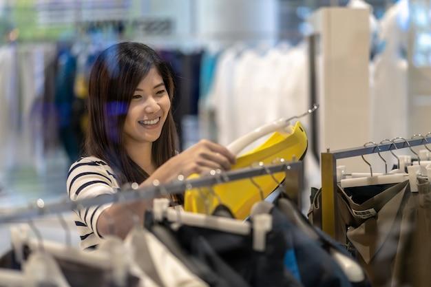 유리 가게 가게에서 옷과 치마를 선택하는 행복 한 아시아 여자