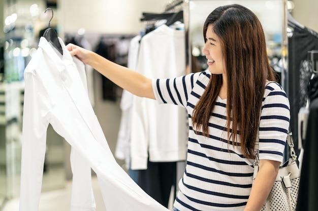 백화점 센터에서 행복한 행동으로 유리 가게 가게에서 옷을 선택하는 행복 한 아시아 여자