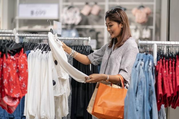 백화점에서 행복한 행동 가게 상점에서 옷을 선택하는 행복 한 아시아 여자