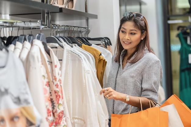 부서 센트에서 행복 한 행동으로 상점 가게에서 옷을 선택하는 행복 한 아시아 여자