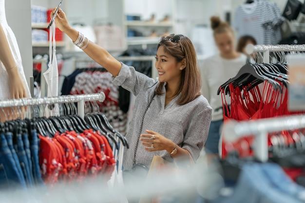 행복 상점 상점 상점에서 유리의 반사와 옷을 선택하는 행복 한 아시아 여자