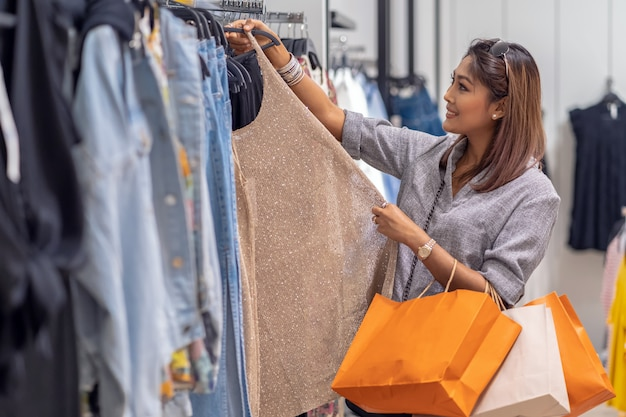 Happy asian woman choosing clothes with in store shop with happy action at department center