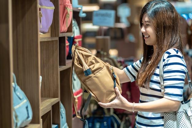 백화점에서 행복한 행동으로 여성 가방 매장을 선택하는 행복 한 아시아 여자