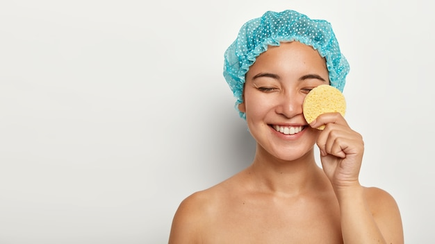 Happy asian woman cleans face with cosmetic sponge, removes makeup, keeps eyes shut, wears protective showercap