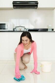 幸せなアジアの女性は台所の床を掃除します