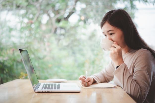 행복한 아시아 여성은 노트북 컴퓨터를 사용하여 커피숍에서 일하는 데 집중했습니다. 자신감 있는 아시아 소녀는 아름다운 미소로 인터넷과 소셜 네트워크를 탐색하기 위해 노트북 컴퓨터를 사용합니다.