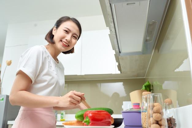 부엌에서 요리하는 행복한 아시아 여성.