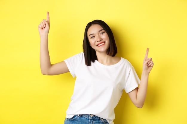 행복 한 아시아 여자 춤과 재미, 노란색에 대 한 흰색 티셔츠에 포즈.