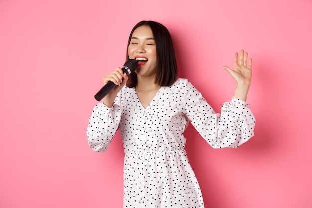 Happy asian woman dancing and singing in microphone, performing at karaoke, standing over pink. copy space