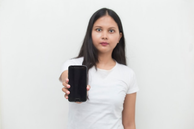 Happy asian woman demonstrating mobile cell phone portrait of smiling girl posing on white background