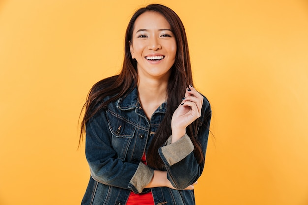 Happy asian woman in denim jacket holding her hair