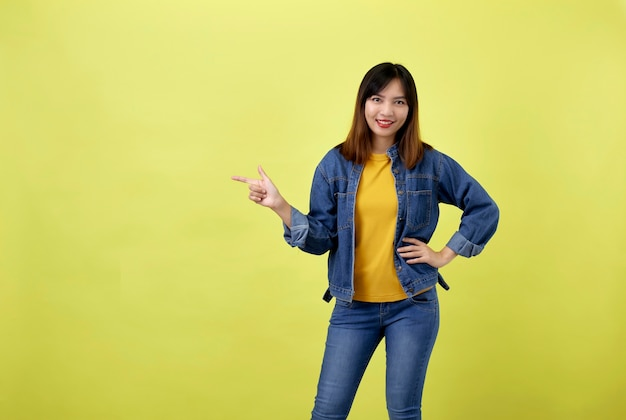 Happy asian woman in denim jacket pointing side to copy space and looking at the camera over yellow space