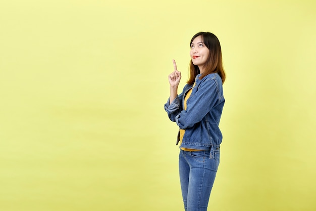 Happy asian woman in denim jacket pointing up to copy space and looking at the camera over yellow space