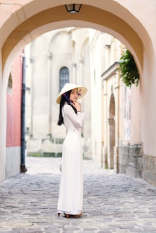Happy asian woman dressed in traditional ao dai white dress with vietnamese conical hat non la, leaf hat.