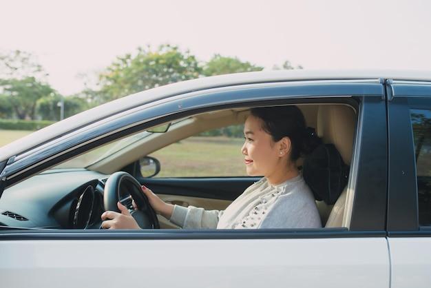 혼자 여행을 운전하는 행복한 아시아 여성.