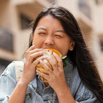 Donna asiatica felice che mangia un hamburger all'aperto