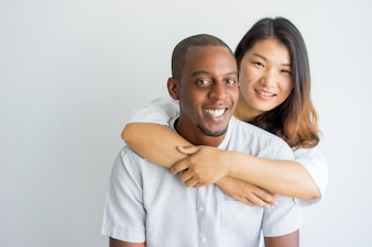 Happy Asian woman embracing handsome African guy and looking at camera.