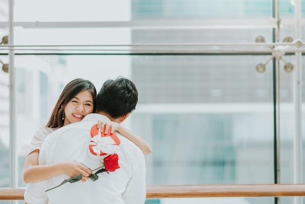 バレンタインギフトを受け取った後に彼女のボーイフレンドを抱きしめているハッピーアジアの女性
