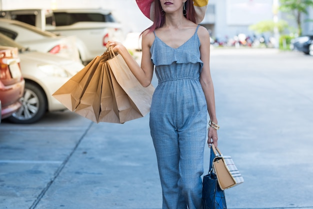 Happy asian woman in fashion casual dress with shopping bags and walking in parking lot.