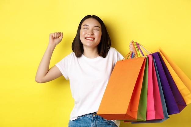黄色の背景の上に立って、販売中の買い物、紙袋を持って、幸せな笑顔でストレッチした後、満足している幸せなアジアの女性。