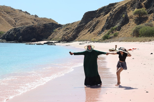 Happy asian woman friends in summer hat enjoying vacation in pink sand beach