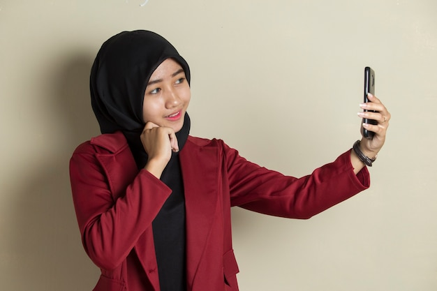 Happy asian woman in hijab with mobile phone making selfie.
