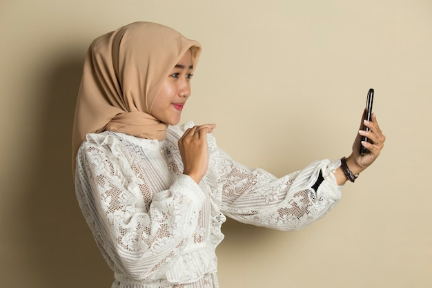 Happy asian woman in hijab with mobile phone making video call.