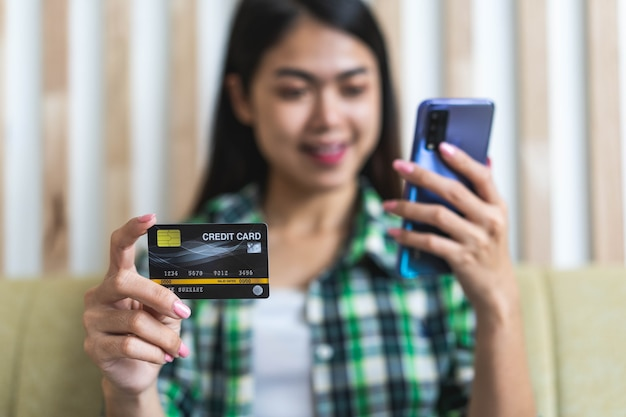 Happy asian woman hold white mockup credit card in hand showing trust and confidence for making payment