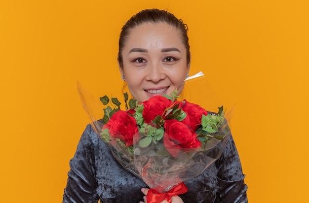 Счастливая азиатская женщина, держащая букет красных роз, глядя вперед, весело улыбаясь, празднует международный женский день, стоя над оранжевой стеной