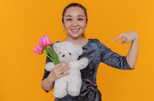 Felice donna asiatica tenendo il mazzo di tulipani rosa e orsacchiotto di puntamento