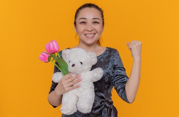 Felice donna asiatica holding bouquet di tulipani rosa e orsacchiotto sorridendo allegramente stringendo il pugno per celebrare la giornata internazionale della donna in piedi sopra la parete arancione