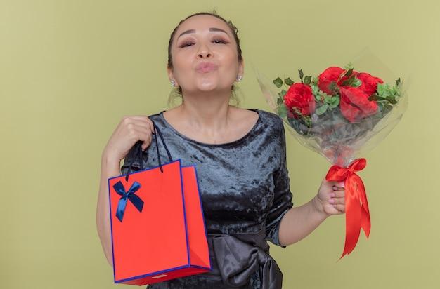 Felice donna asiatica che tiene il mazzo di rose rosse e sacchetto di carta con il regalo che soffia un bacio che celebra la giornata internazionale della donna in piedi sopra la parete verde