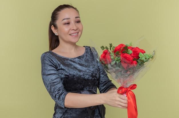 Felice donna asiatica tenendo il mazzo di rose rosse sorridendo allegramente celebrando la giornata internazionale della donna in piedi sopra la parete verde