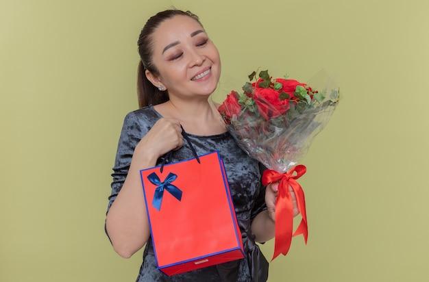 Donna asiatica felice che tiene il mazzo delle rose rosse che sorride allegramente e sacchetto di carta con il regalo che celebra la giornata internazionale della donna in piedi sopra la parete verde