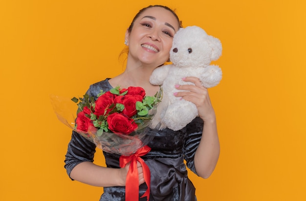 Happy asian woman holding bouquet of red roses and teddy bear as a gift smiling cheerfully celebrating mother's day standing over orange wall
