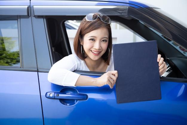 Счастливая азиатская женщина держа книгу документа страхования автомобилей и сидя в концепции персоны автомобиля, корабля безопасности и защиты клиента