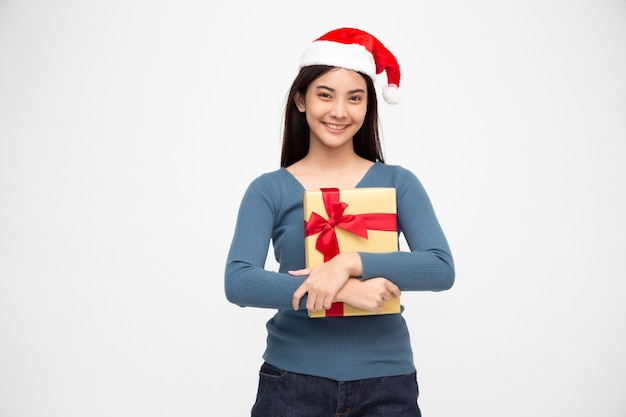 Happy asian woman holding gold gift box and wearing santa hat.