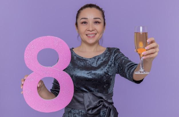 紫色の壁の上に立って国際女性の日を祝って元気に笑って段ボールとシャンパングラスで作られた8番を保持している幸せなアジアの女性
