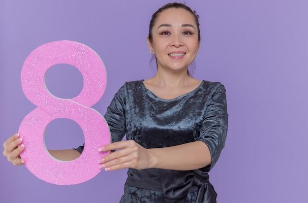 紫色の壁の上に立っている国際女性の日を元気に祝って笑顔で正面を見て段ボールから作られた8番を保持している幸せなアジアの女性