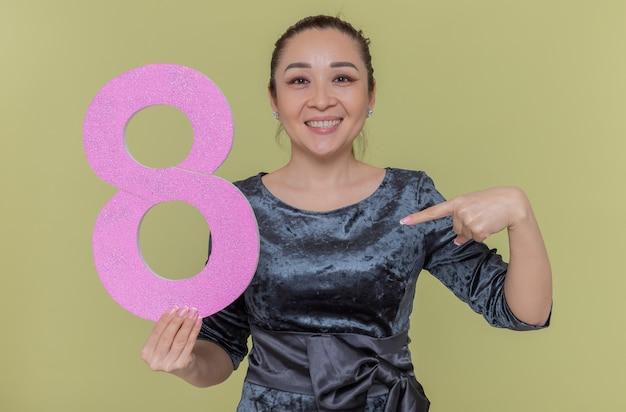 緑の壁の上に立って国際女性の日を祝って元気に笑って人差し指で指している段ボールから作られた8番を保持している幸せなアジアの女性