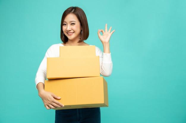 パッケージ宅配ボックスを押しながら[ok]を示す幸せなアジアの女性、配送宅配便および配送サービスのコンセプト