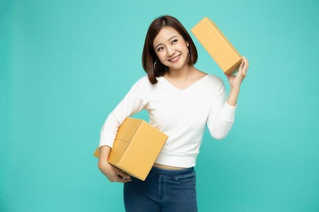 パッケージ宅配ボックス、配達宅配便および出荷サービスのコンセプトを保持している幸せなアジアの女性