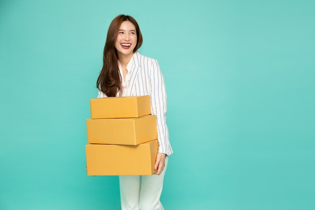 Happy asian woman holding package parcel box isolated on light green background, delivery courier and shipping service concept.