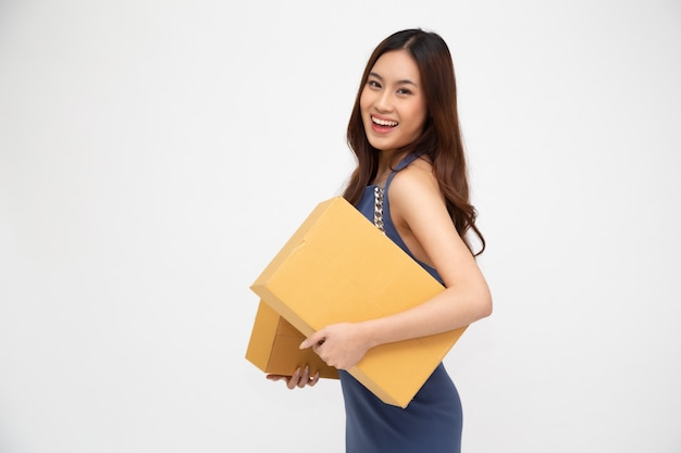 白い壁、配達宅配便および出荷サービスのコンセプトに分離されたパッケージ宅配ボックスを保持している幸せなアジアの女性