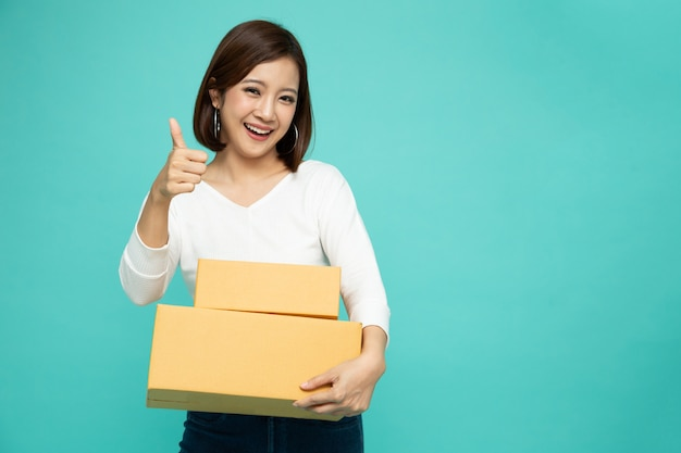 Happy asian woman holding package parcel box and thumb up on green color