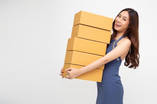 パッケージ宅配ボックスを保持している幸せなアジアの女性。