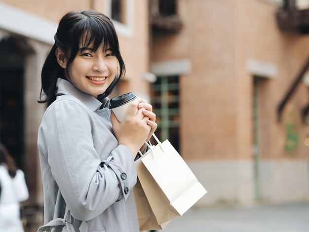 Happy asian woman holding shopping bag.