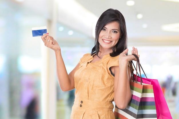 ショッピングバッグやクレジットカードを保持している幸せなアジアの女性