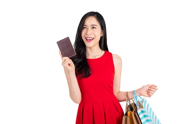 Happy asian woman holding shopping bags and showing passort in another hand