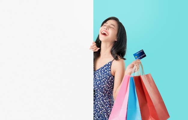 Happy asian woman holding shopping bags with credit card and showing blank signboard.
